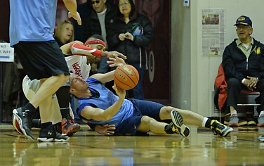 Hoonah's Author Campbell and James Gang's Jim Carson battle for a loose ball during their C-Bracket elimination game at the Juneau Lions Club 71st Annual Gold Medal Basketball Tournament at Juneau-Douglas High School on Thursday. James Gang won 71-50. (Photo courtesy Klas Stolpe)