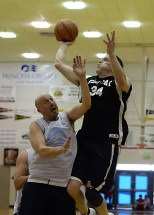 Yakutat's Jimmy Jensen (34) scores over James Gang's Jim Carson (20) in a C-Bracket elimination game in the Juneau Lions Club 71st Annual Gold Medal Basketball Tournament at Juneau-Douglas High School on Wednesday. James Gang won 70-62. (Photo courtesy Klas Stolpe)