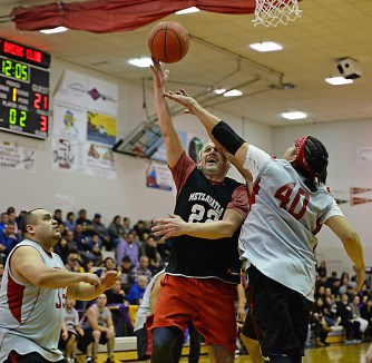 Metlakatla's Archie Dundas (22) scores over Angoon's Albert Kookesh (35) and Travis See (40) in a C Bracket game the Juneau Lions Club 71st Annual Gold Medal Basketball Tournament at JDHS on Sunday, March 19, 2017. Metlakatla won 85-72. (Photo courtesy Klas Stolpe)
