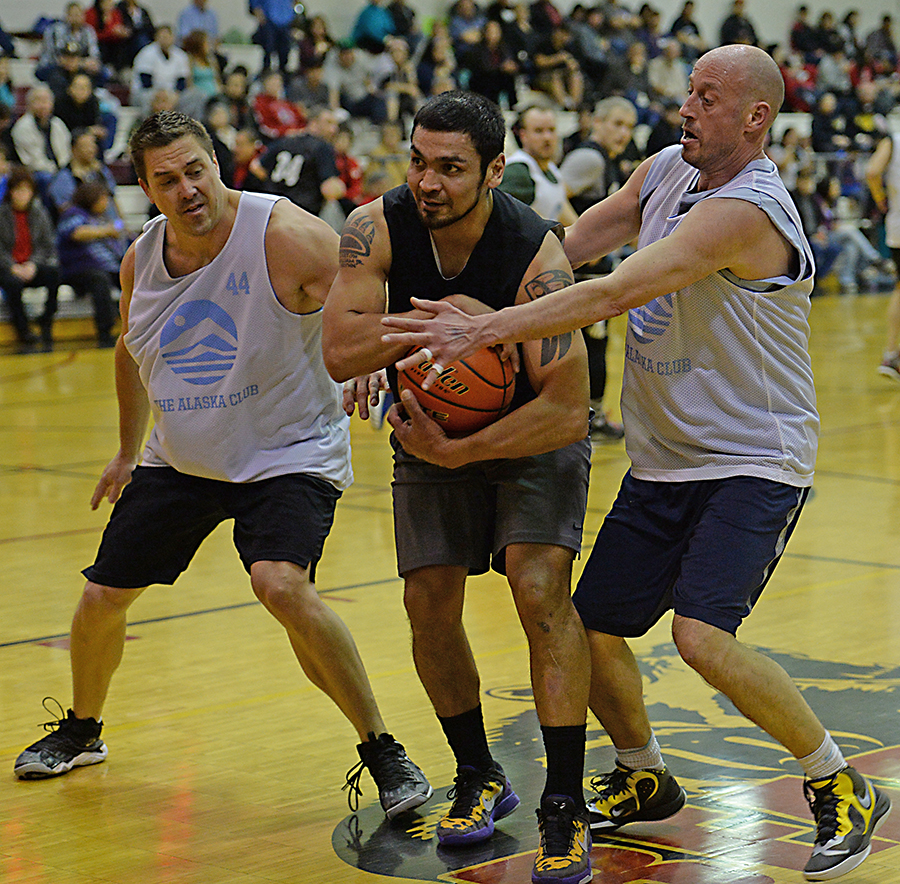 Metlakatla's Willie Hayward secures a ball as James Gang's Russ Stevens and Jim Carson defend during their C-Bracket elimination game in the Juneau Lions Club 71st Annual Gold Medal Basketball Tournament at Juneau-Douglas High School on Friday. James Gang won 84-74. (Photo courtesy Klas Stolpe)