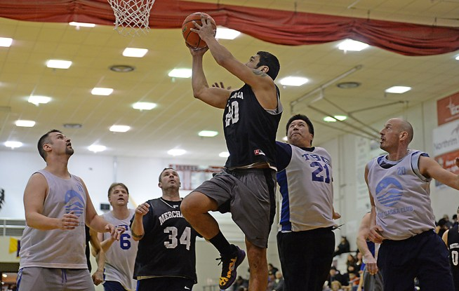 Metlakatla's Willie Hayward (20) scores against James Gang's Ray Zimmer (34), Al Tagaban (21) and Jim Carson (20) during their C-Bracket elimination game in the Juneau Lions Club 71st Annual Gold Medal Basketball Tournament at Juneau-Douglas High School on Friday. James Gang won 84-74. (Photo courtesy Klas Stolpe)