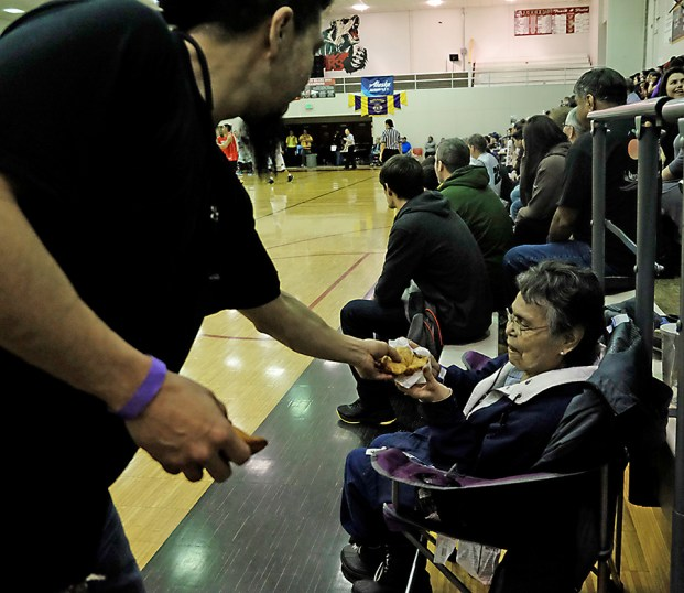 A fan gets free fry bread during the Juneau Lions Club 71st Annual Gold Medal Basketball Tournament at Juneau-Douglas High School on Saturday. (Photo courtesy Klas Stolpe)