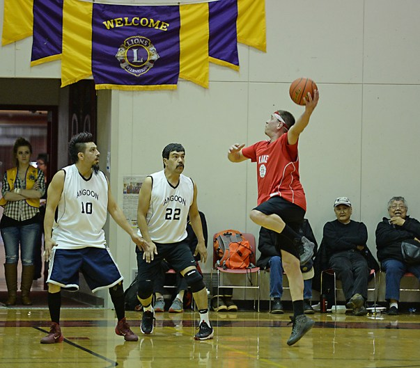 Kake's Nick Davis shoots his patented sky hook against Angoon's Marti Fred (10) and Edward Jack (22) during their Masters Bracket elimination game in the Juneau Lions Club 71st Annual Gold Medal Basketball Tournament at Juneau-Douglas High School on Friday. Kake won 94-67. (Photo courtesy Klas Stolpe)