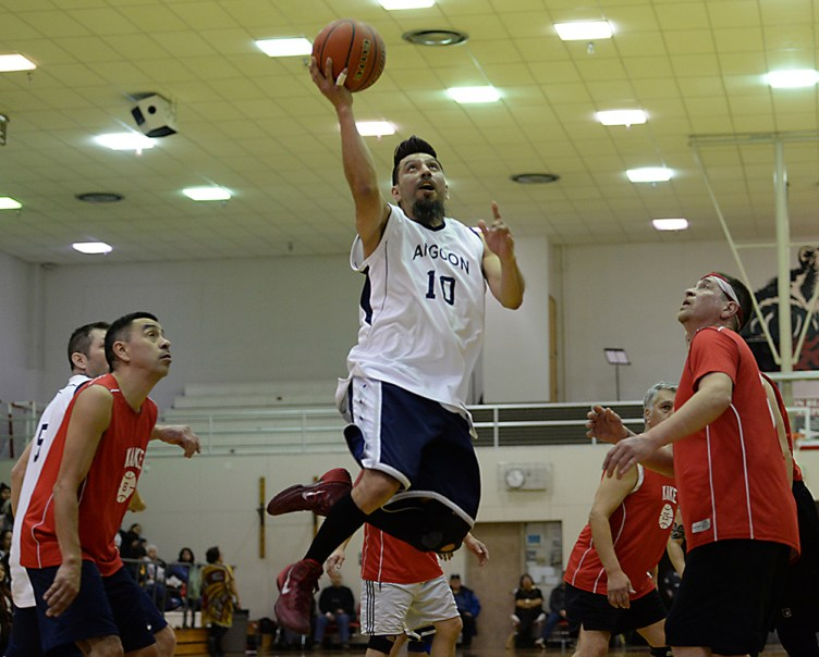 Angoon's Marti Fred (10) scores over Kake's Jay Peterson (8) and Nick Davis during their Masters Bracket elimination game in the Juneau Lions Club 71st Annual Gold Medal Basketball Tournament at Juneau-Douglas High School on Friday. Kake won 94-67. (Photo courtesy Klas Stolpe)