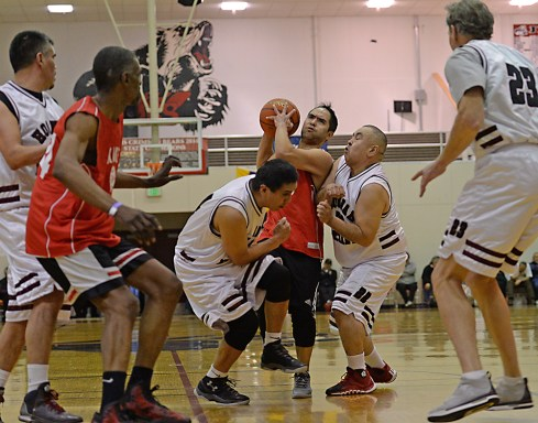 Kake's Rudy Bean is fouled by Hoonah's Ken Willard and Duane Jack Sr. during the Master's Bracket championship of the Juneau Lions Club 71st Annual Gold Medal Basketball Tournament at Juneau-Douglas High School on Saturday. Hoonah won 80-78. (Photo courtesy Klas Stolpe)