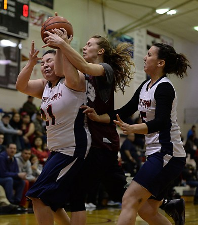 Yakutat's Martha Mallott (21) and Kim Buller (5) battle for a rebound with Haines' Lisa Shove during their Womens Bracket semifinal in the Juneau Lions Club 71st Annual Gold Medal Basketball Tournament at Juneau-Douglas High School on Thursday. Haines won 65-52. (Photo courtesy Klas Stolpe)