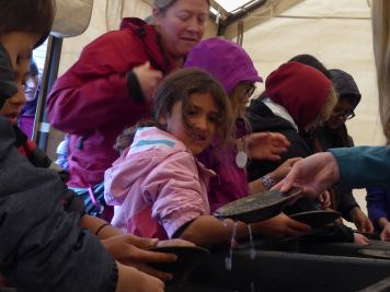 A group of children try their hand at gold panning at Juneau Gold Rush Days on Saturday.