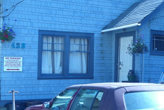 A blue house with the number 423. A red car sits in front of it.
