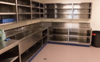 A shiny metal commercial kitchen area - counter and sink with shelves above and below it