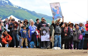 Members of the Yanyeidí clan hold pictures of their mothers and grandmothers as they watch the installation of the wolf totem pole at Savikko Park. June 6, 2018. (Photo by Adelyn Baxter/KTOO)