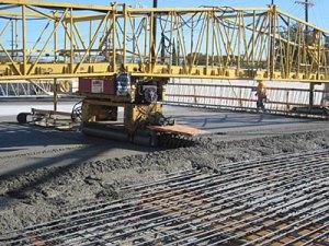 Maquina de colado de concreto (Bidwell) pone el nuevo concreto sobre la superficie del puente.