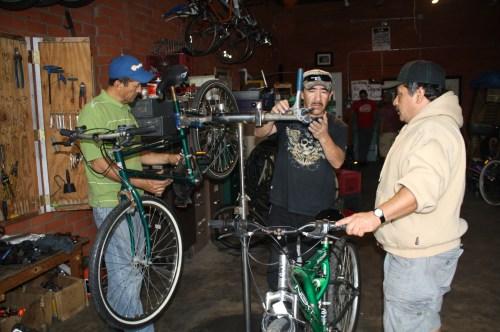 José de La Torre, izquierda, repara una bicicleta, mientras que Rafael Guerrero, centro, ayuda a Marín Flores con su bicicleta. (Foto Agustín Durán/El Pasajero)