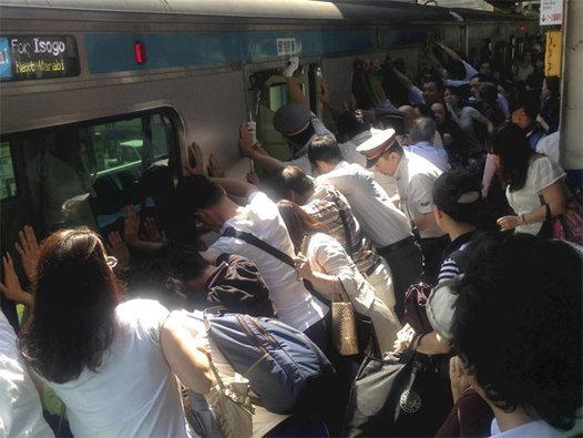 Docenas de personas empujan un tren de pasajeros en Japón para liberar a una mujer atrapadas. Foto: Norihiro Shigeta/Yomiuri Shimbun.