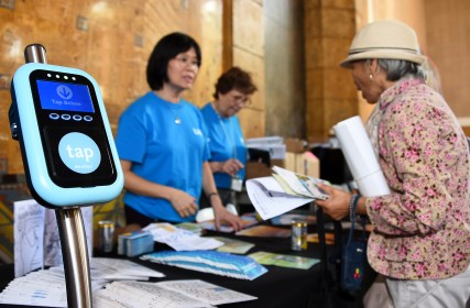 Visitor with TAP card demonstration tool at Metro First older Adult Transportation Expo.