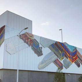 Artwork on the façade of Maintenance of Way facility, entitled Getting There, Ball-Nogues Studio. The artwork is comprised of over 30,000 acrylic chips, with the images of trains, buses and rail cars blurring and focusing depending on the viewing angle and angle of the sun.