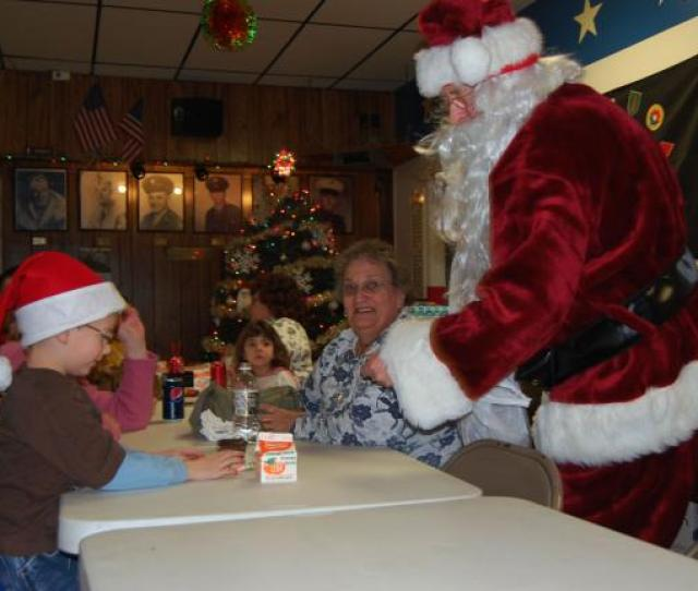 Two Santas Meet Across The Table As Skylar Green Dons His Hat