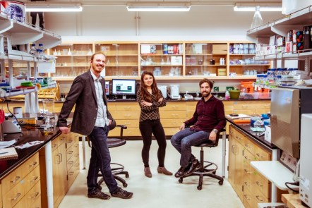 Three people standing in a laboratory