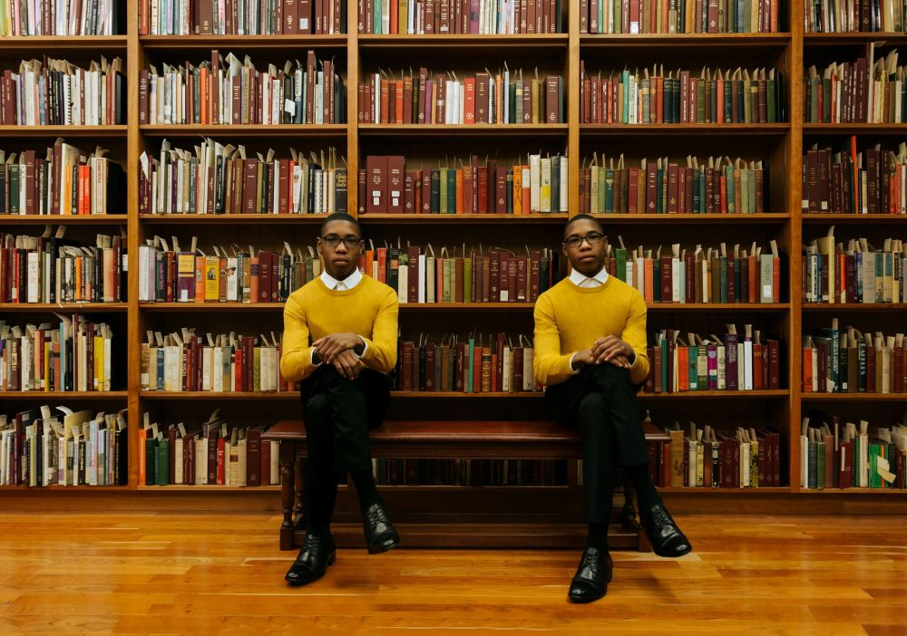 twins sitting in front of a bookshelf in a library