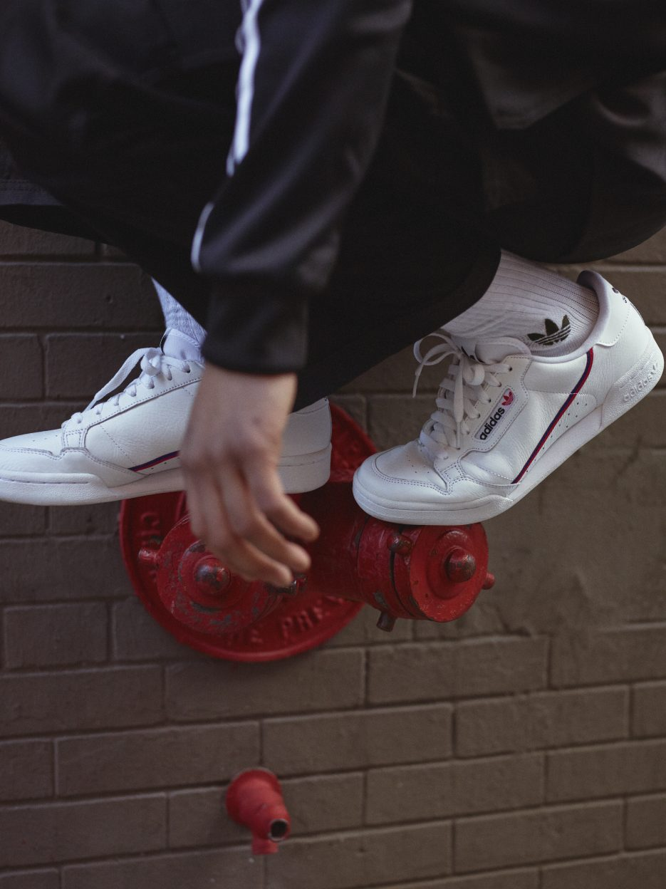 A person standing on a fire hydrant wearing Adidas Continental 80 sneakers