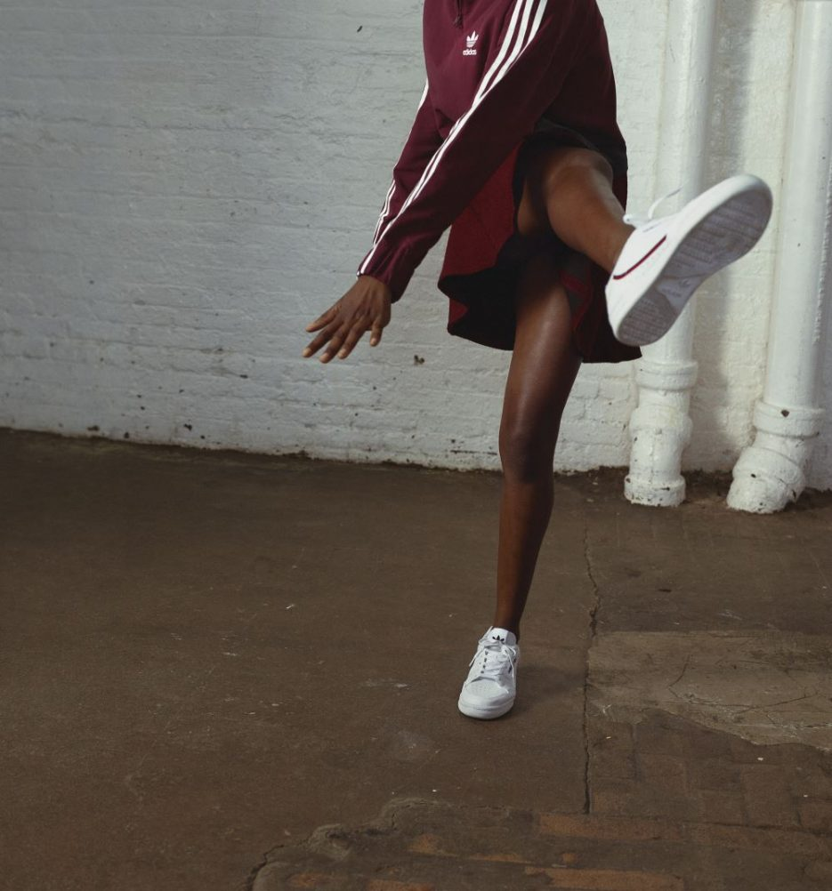 A woman wearing maroon kicking with Adidas Continental 80 sneakers one