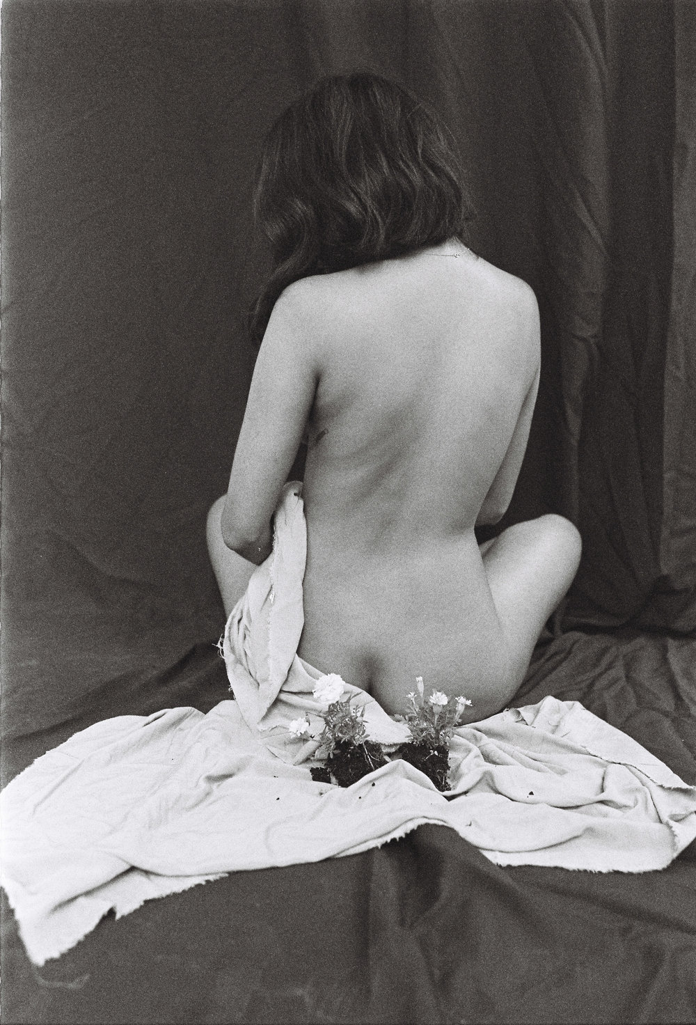 Tyra Naidoo nude from behind holding a blanket with with flowers laying behind her