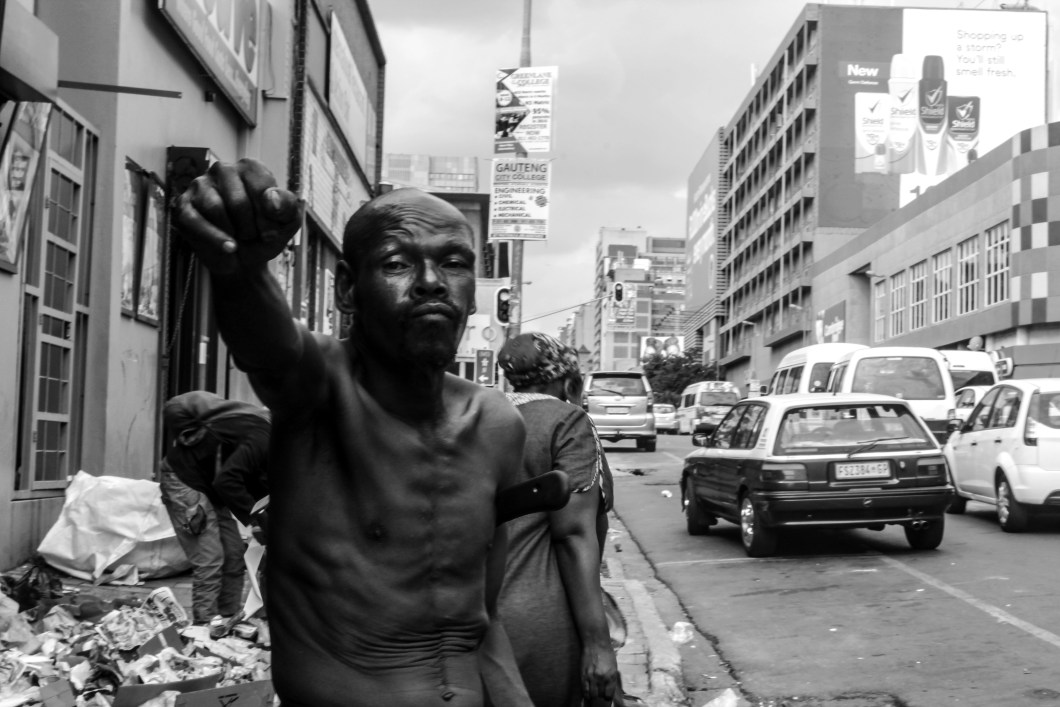 Black and white photo of a shirtless man in the street taken by Toka Hlongwane