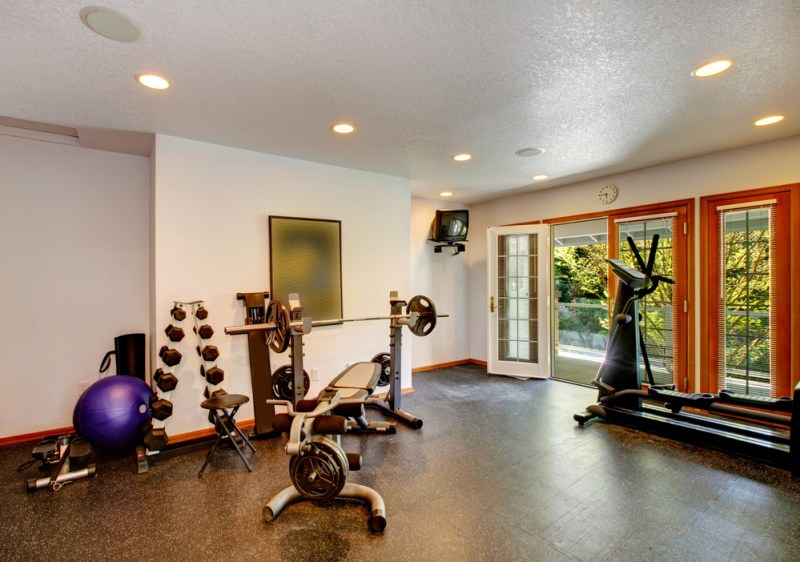 Large exercise space with dumbbells and cardio machine with doors to the outside