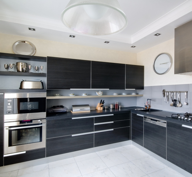 Dark kitchen cabinets with white floor and walls with stainless steel appliances