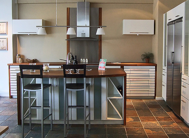 Silver kitchen cabinets with stylish island and rust-colored tile flooring