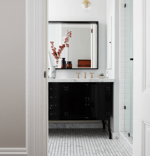 Bathroom with framed mirrored and marble vanity