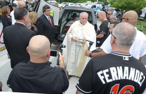 El rector de la Ermita de la Caridad del Cobre, el padre Juan Rumín Domínguez, se prepara para bendecir el ataúd del jugador cubano (EFE)