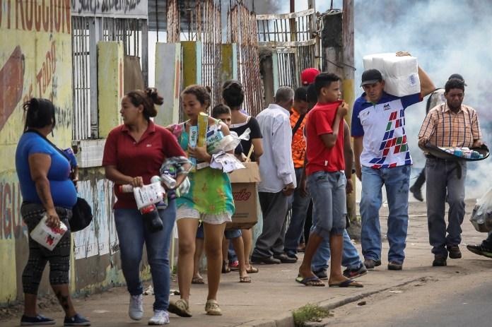 Pobladores de Ciudad Bolívar se llevan algunos productos básicos que pudieron tomar de unos de los supermercados que fue saqueado el fin de semana pasada antes las escasez de alimentos y otros productos que aqueja a Venezuela. REUTERS/William Urdaneta
