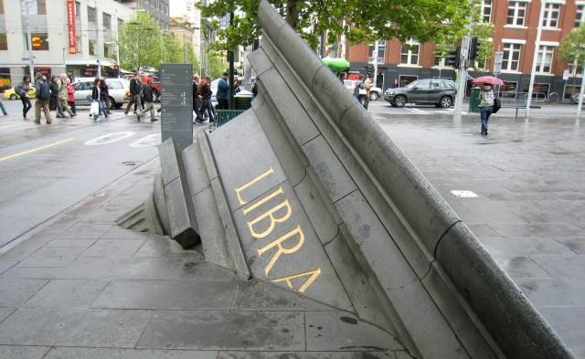 """""""The Architectural Fragment"""" de Petrus Spronk se encuentra en Melbourne, Australia, y muestra una biblioteca que parece enterrada en el asfalto de la ciudad. Simboliza la decadencia de la civilización"""