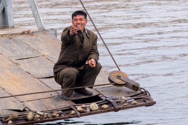 Un soldado fronterizo gesticula hacia un barco de turistas. Cada día, cientos de ciudadanos chinos navegan para asomarse y tomar una mirada al régimen de Kim