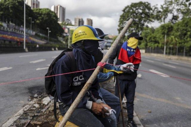 La Guardia Nacional Bolivariana (GNB) disparó gases lacrimógenos para dispersar a la gente que cortaba vías en Caracas (EFE)
