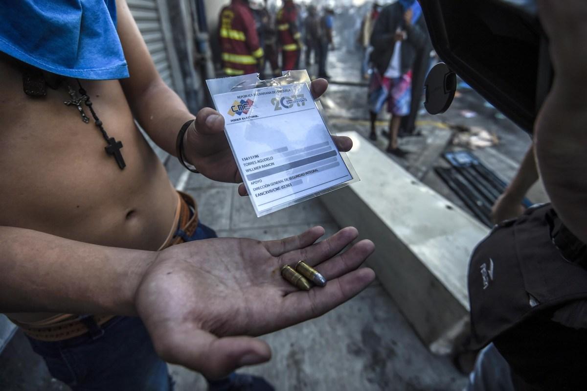 Un manifestante muestra las balas que usó durante la jornada de votación las fuerzas represivas de Maduro (AFP)