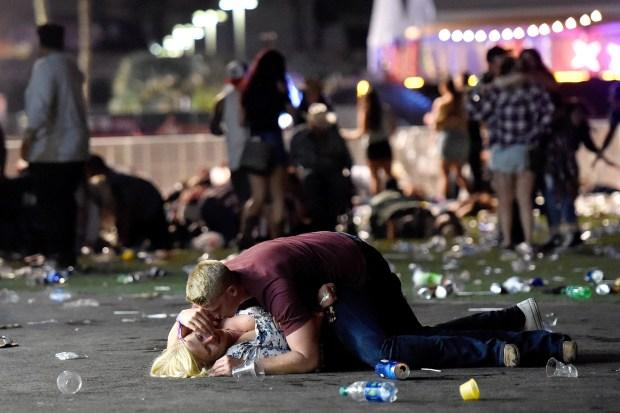 Un hombre consuela y protege a una mujer herida durante la masacre de Las Vegas. Luego se conocería la identidad del joven: Matthew Cobos, marine (Getty Images)