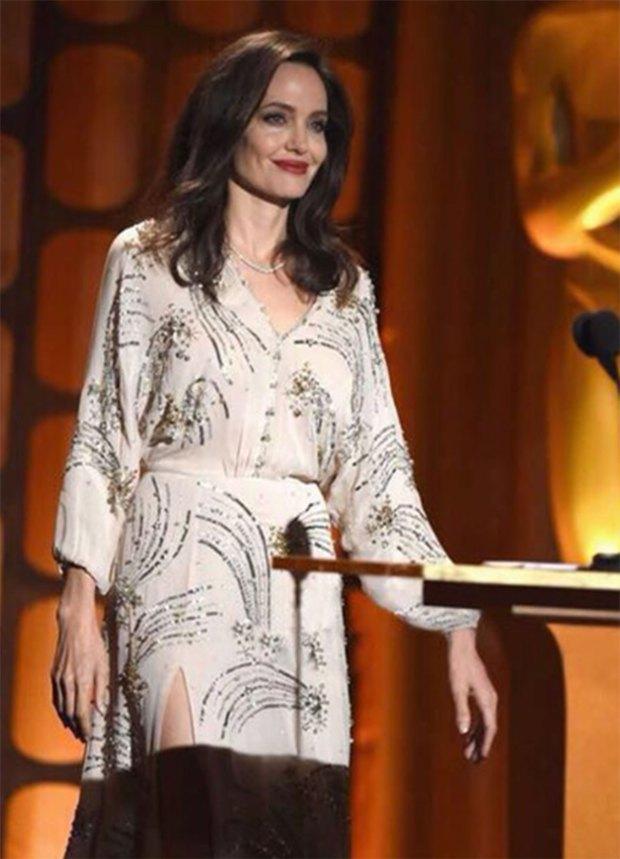 Radiante, Jolie con su vestido de mangas largas bordado con piedras.