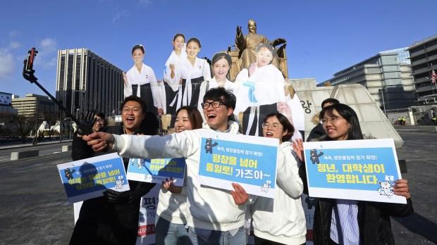 Estudiantes surcoreanos posan junto a imágenes de las famosas porristas del Norte (AP)