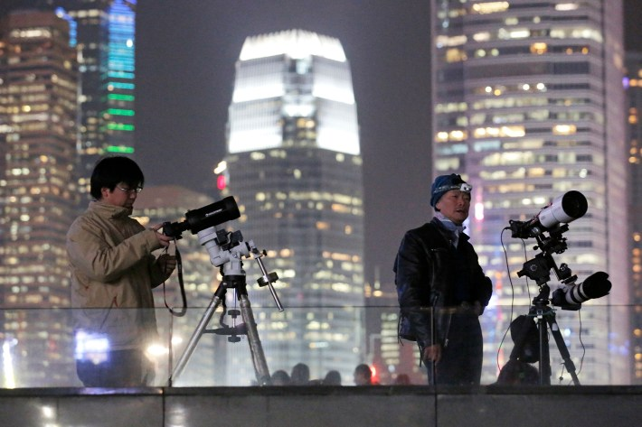 Un astrónomo de Hong Kong utiliza un telescopio para observar la luna a lo largo del Victoria Harbour en Hong Kong, el miércoles 31 de enero de 2018