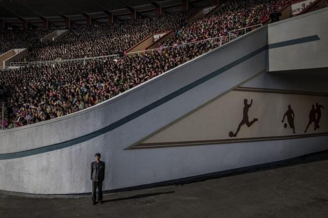North Korea – Corea del Norte: una multitud espera la salida del Maratón de Pyongyang en el Estadio Kim Il-sung, mientras que un oficial vigila la salida, en Pyongyang, Corea del Norte. (Roger Turesson, Suecia)