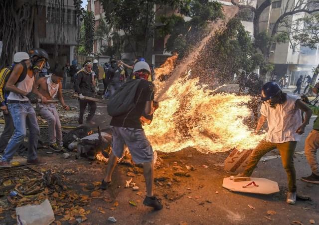 Demonstrator Catches Fire – El manifestante se incendia: un manifestante se prende fuego después de que el tanque de gasolina de una motocicleta policial explote, durante una protesta contra el presidente venezolano Nicolás Maduro, en Caracas. (Juan Barreto, Venezuela)