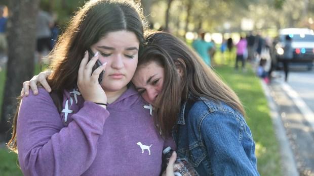 Dos amigas se abrazan tras la masacre en Marjory Stoneman Douglas (AFP)