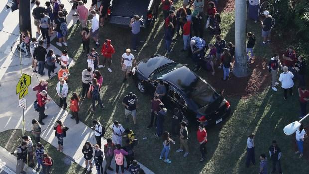 Los estudiantes en las afueras de la escuela tras evacuar el instituto (AFP)