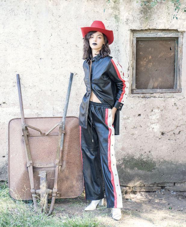 Sombrero de paño, camisa y pantalón de cuero con broches (Cher) y botas de charol ($ 5.879, Paruolo).