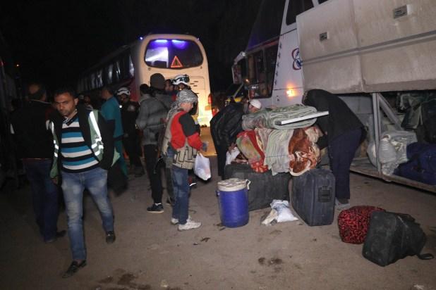 Civiles sirios descargan sus pertenencias devlos autobuses en la ciudad de Qalaat al Madiq tras evacuar Guta Oriental(AFP)