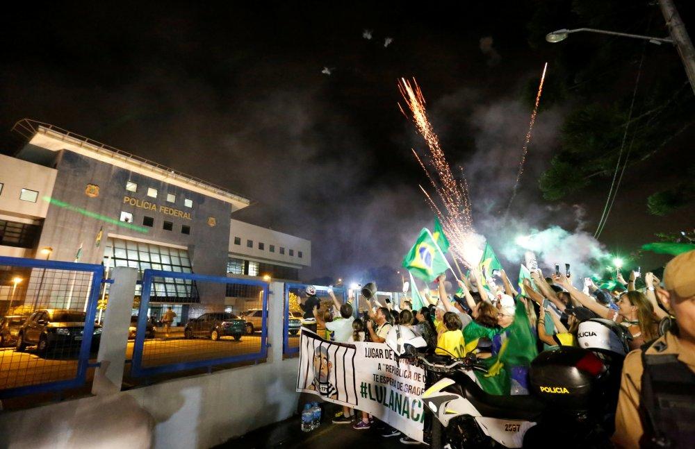 Manifestantes protestan en contra del ex presidente brasileño Luiz Inácio Lula da Silva a las afueras del Departamento de la Policía Federal al que fue trasladado la noche del sábado 7 de abril de 2018 en Curitiba, Brasil. (AP Foto/Denis Ferreira)