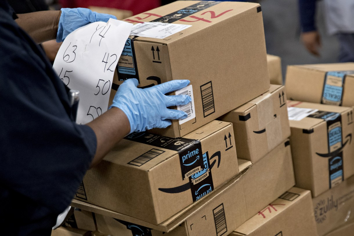 An employee arranges Amazon.com Inc. packages before delivery at the United States Postal Service Joseph Curseen Jr. and Thomas Morris Jr. processing and distribution center in Washington. MUST CREDIT: Bloomberg photo by Andrew Harrer