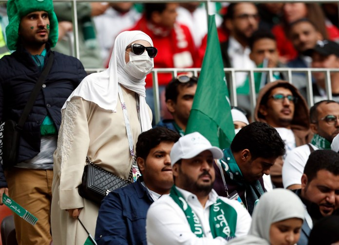 Una hincha de Arabia Sauditacon casi todo su rostro cubierto en contraste con el resto de los asistentes al estadio donde se jugará la final y una de las semifinales(AP Photo/Pavel Golovkin)