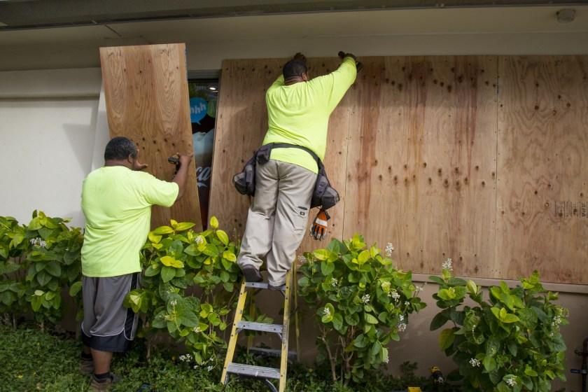 Trabajadores instalan tablas para proteger los vidrios de los comercios en Honolulu (AFP)